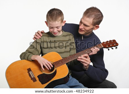 mid-adult father smiling and teaching elementary age son how to play guitar