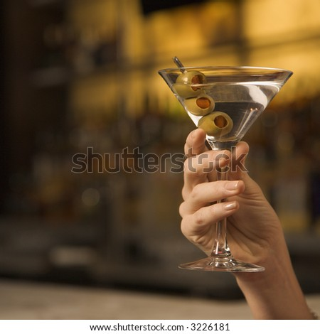 Mid adult female Caucasian hand holding a martini with three olives.