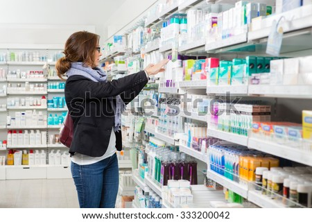 Mid adult female customer choosing product at pharmacy