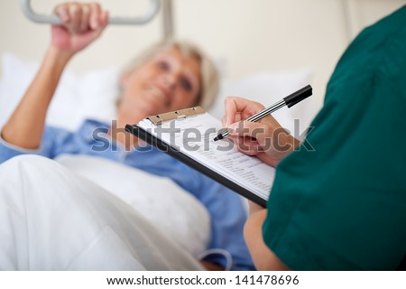Mid adult female nurse writing on clipboard while looking at patient in hospital
