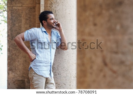 mid adult hispanic man talking on mobile phone and leaning on columns outdoors. Horizontal shape, side view, copy space