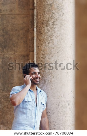 mid adult hispanic man talking on mobile phone and leaning on columns outdoors. Verticl shape, side view, copy space