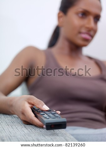 stock photo mid adult indian woman on sofa changing tv channel with remote control front view copy space 82139260 Want a erotic vacation like this book now!