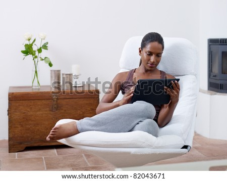 mid adult indian woman relaxing on armchair and using touch pad computer. Horizontal shape, front view, copy space