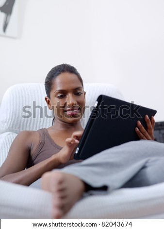 stock photo mid adult indian woman relaxing on armchair and using touch pad computer vertical shape front 82043674 New 'Adult Video' Channel Added To Google TV