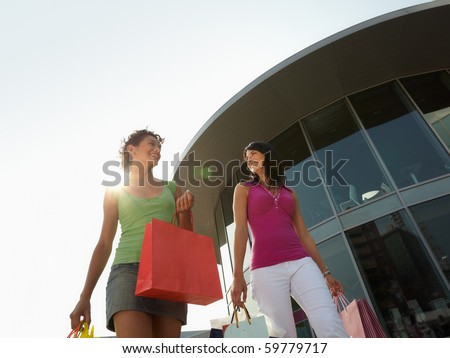 mid adult italian woman and hispanic woman carrying shopping bags out of shopping center at sunset. Horizontal shape, low angle view, copy space