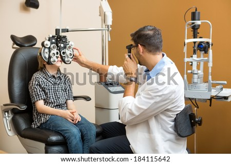 Mid adult male optometrist examining preadolescent boy\'s eyes in clinic