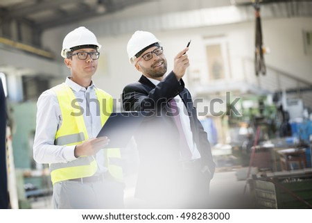 Mid adult male supervisors having discussion in metal industry
