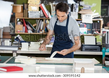 Mid adult male worker working at table in paper industry