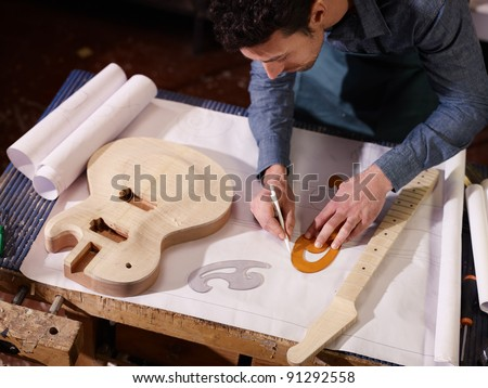 mid adult man at work as craftsman in italian workshop with guitars and blueprints, drawing sketches. High angle view