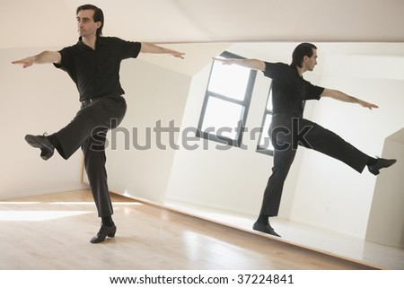 Mid adult man dancing in front of a mirror doing Jazz Kick