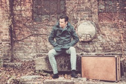 Mid adult man in coat with hands in pockets sitting on a wall with leather suitcase and waiting for someone.