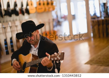 Mid-adult man playing an acoustic guitar inside a music store.