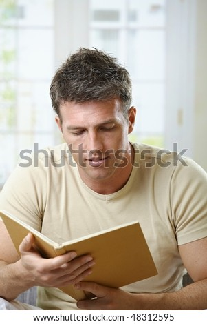 Mid-adult man reading at home sitting on couch with book handheld.