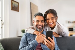 Mid adult man relaxing on sofa and showing new app to african american wife on cellphone. Middle eastern man and woman sitting on couch at home and using mobile phone to do a video call with family.