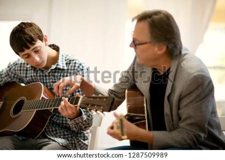 Mid adult man teach a teenage boy how to play guitar.