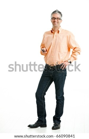 Mid-adult man wearing jeans and orange shirt standing and holding mobile phone. Isolated on white.? - stock photo