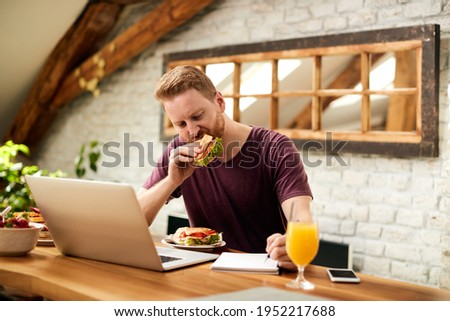 Mid adult man working at home and writing n notebook while eating sandwich for breakfast. Foto stock ©