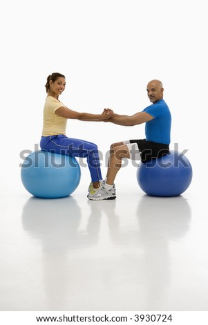 Mid adult multi-ethnic man and woman balancing on blue exercise balls with hands and feet locked together smiling and looking at viewer.