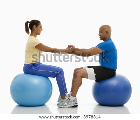 Mid adult multiethnic man and woman balancing on blue exercise balls facing each other with hands and feet locked together.