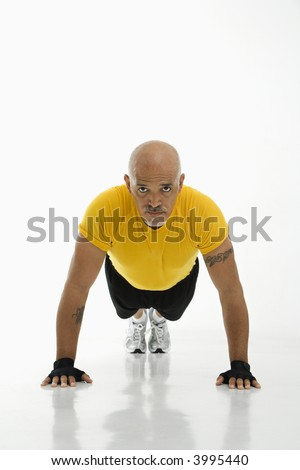 Mid adult multiethnic man wearing yellow exercise shirt doing pushups while looking at viewer.