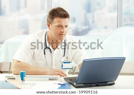 Mid-adult physician working with laptop in office.?