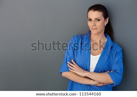 Mid-adult pretty woman posing, smiling at camera, grey background, copyspace.