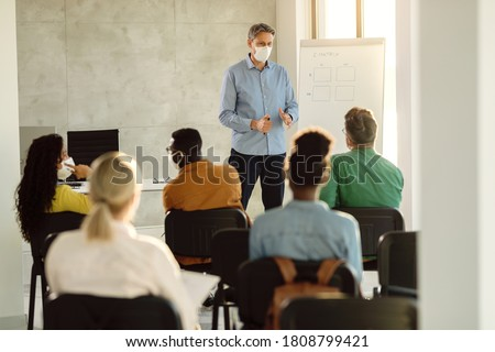 Mid adult professor wearing face mask while talking to a group of college students in lecture hall.