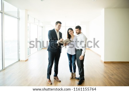 Mid adult realtor explaining agreement to couple in new apartment