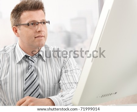 Mid-adult smart businessman looking at computer screen in office?