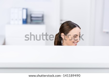 Mid adult smiling businesswoman in office cubicle