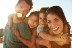 Mid adult white parents piggybacking their kids on a beach, smiling to camera, close up, lens flare