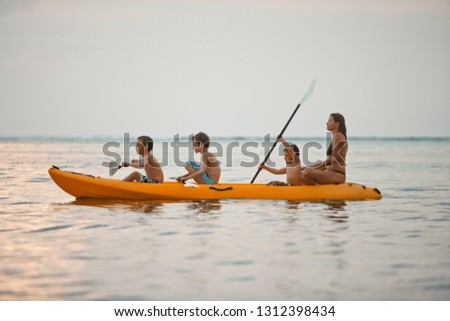 Mid adult woman and her three sons kayaking in a kayak together in the sea.