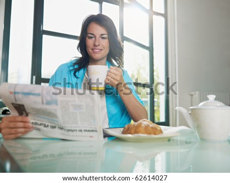 mid adult woman drinking coffee and reading news. Horizontal shape, copy space