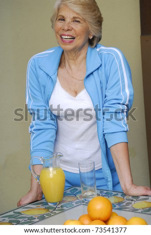 Mid adult woman drinking orange juice. Mid adult woman holding fresh oranges.