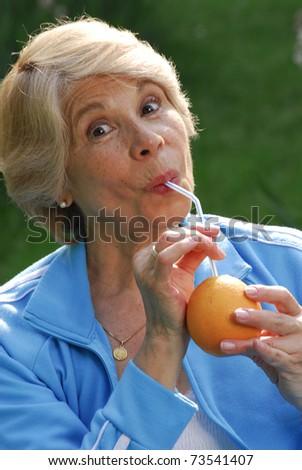 Mid adult woman drinking orange juice. Mid adult woman holding fresh oranges.