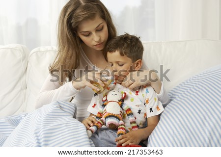 Mid adult woman feeding juice to her son