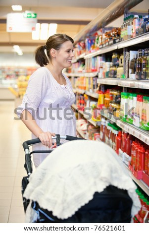 stock photo : Mid adult woman holding baby stroller and looking at products ...