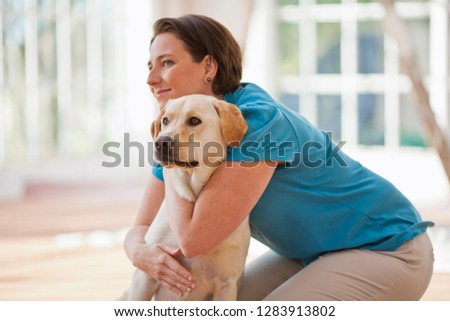Mid adult woman kneeling with her arms around a labrador dog.