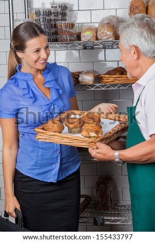 Mid adult woman looking at senior salesman holding tray of muffins at grocery store