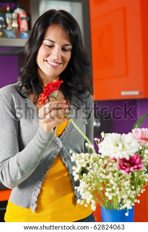 mid adult woman putting gerbera in blue pot. Vertical shape, front view, waist up