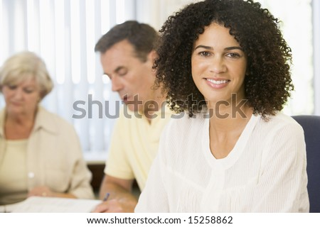 Mid adult woman studying with other adult students