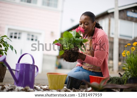 Mid-adult woman tending to her garden outside her home.