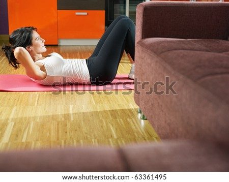 mid adult woman training abdominals at home. Horizontal shape, full length, side view, copy space