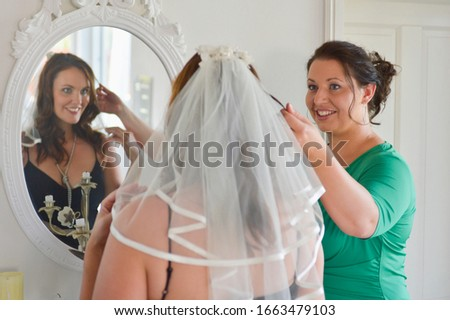 Mid adult woman trying on wedding veil with friend