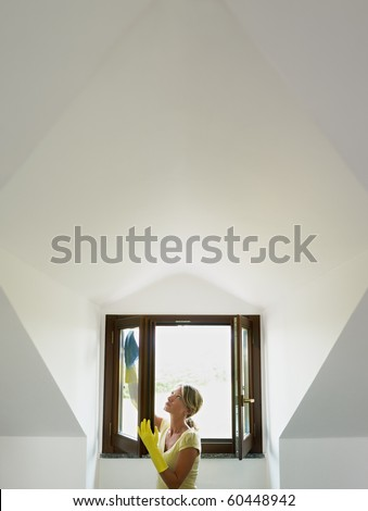 mid adult woman wiping windows in mansard. Vertical shape, waist up, copy space