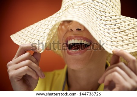 mid adult woman with straw hat smiling and having fun on red background