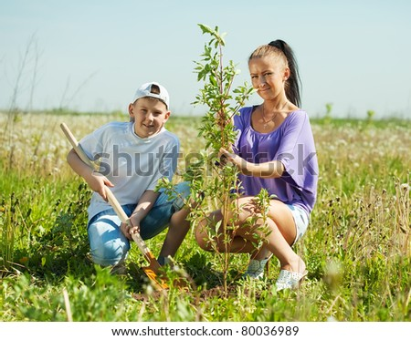 Mid adult woman with  teenager son setting tree outdoor