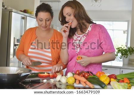 Mid adult women in kitchen preparing food