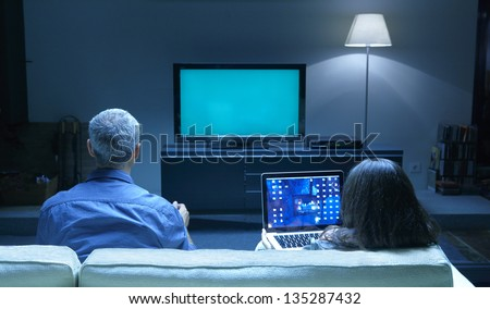 Mid Adults watching TV and PC blue tone